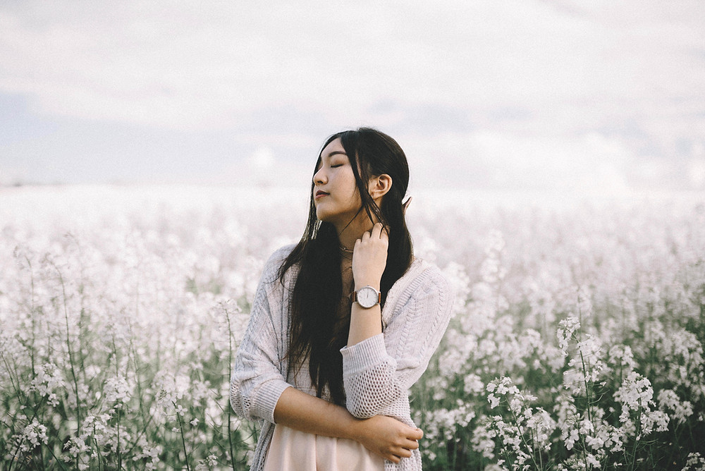 Peaceful woman in a field of white flowers