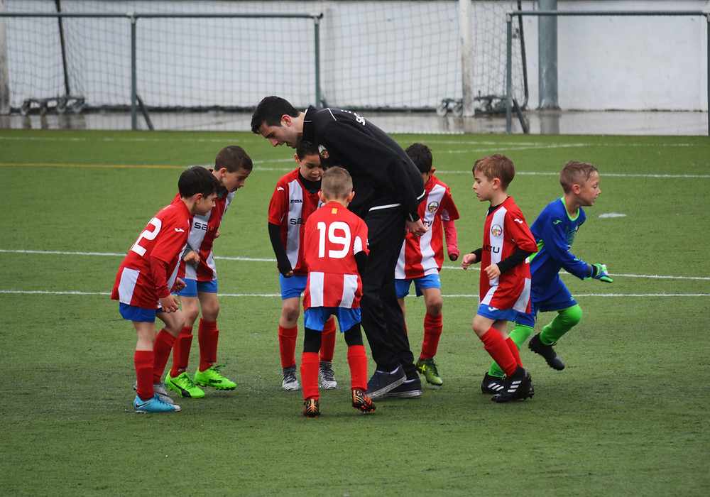 kids learning to play football with a coach on an outdoor football pitch