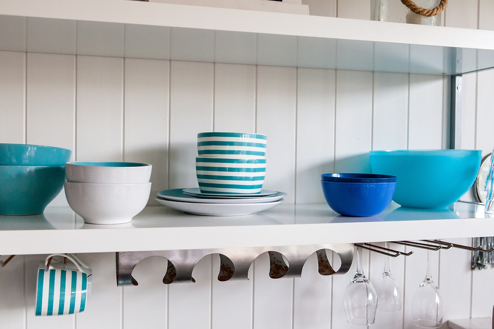 White open shelves with blue bowls and plates on top
