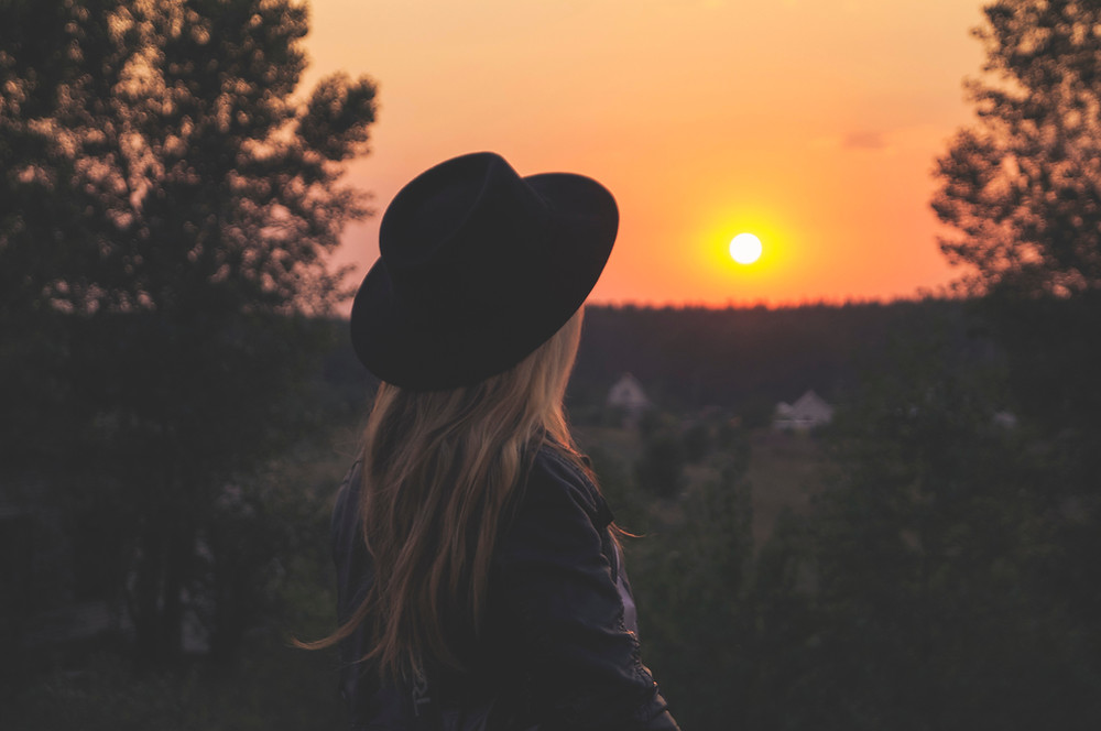 Woman with hat on enjoying a view of the sunrise