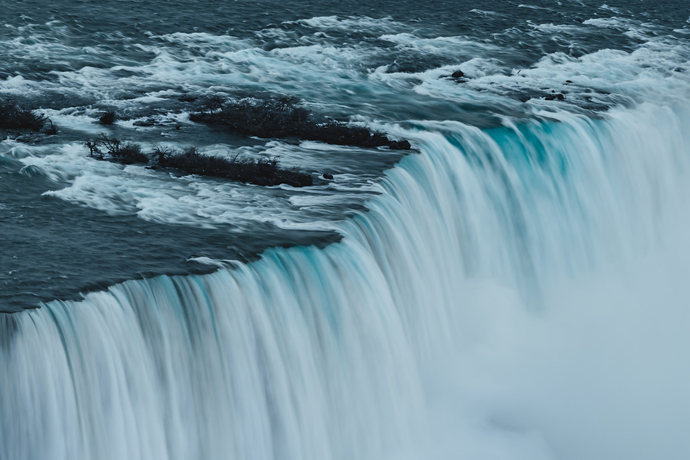 The Grey water flows over the edge of the waterfall, creating a white curtain effect down the face of the falls.