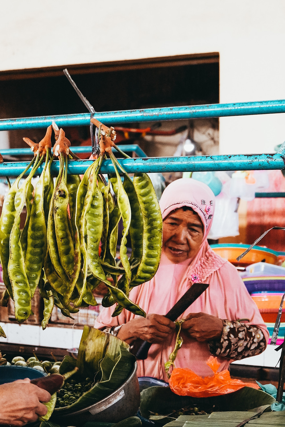 Peteh (pete or petai in Indonesian) beans in strings at a food market in Indonesia