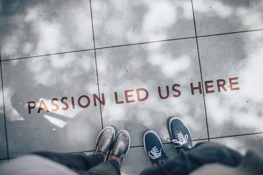 "two people's feet near a painted sentence on sidewalk saying ""passion led us here"""