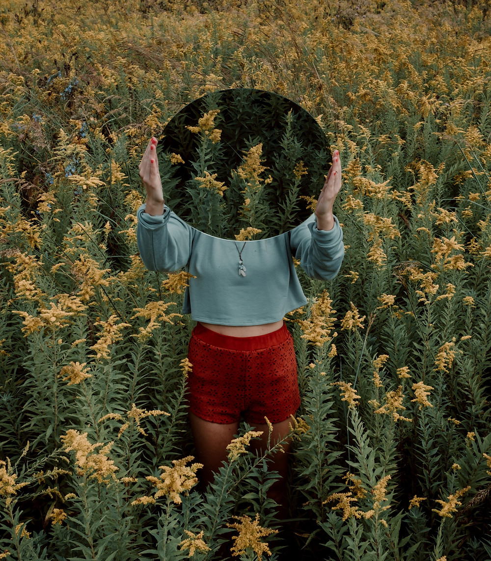 A person standing in a field of golden rod holding a mirror in front of their face that shows a reflection of the field