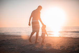 Trusting young son walks hand in hand with his parent on the beach.