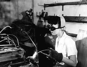 Vintage black and white photo of young 1940s woman welding