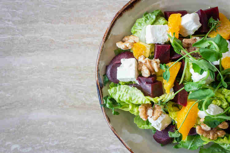 fresh organic salad featuring beets, orange segments, baby lettuces, and crumbled cheeses