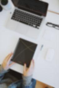 mani di donna su rubrica e di fronte al laptop