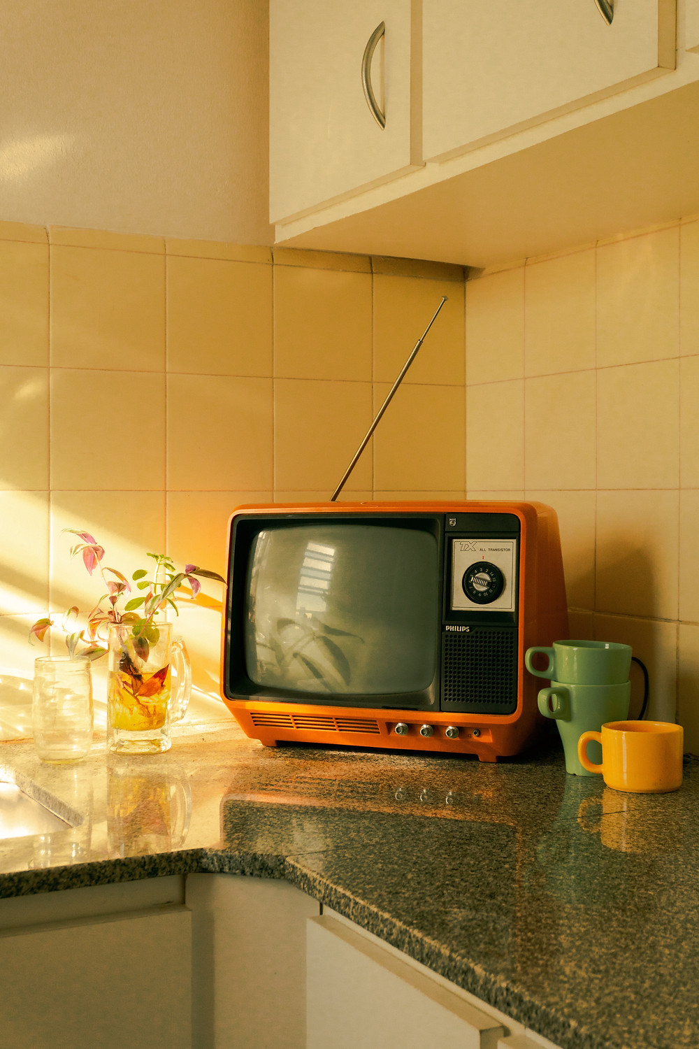 retro TV on top of kitchen counter next to colorful mugs