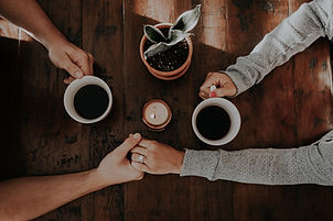 Couple holding hands while drinking coffee, happy, close and satisfied.