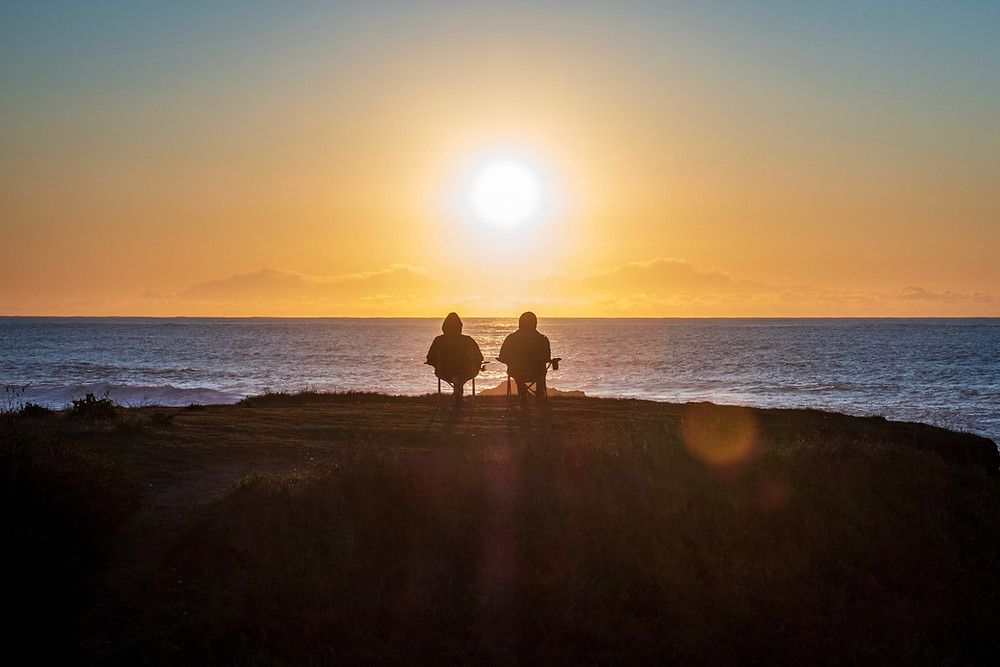 couple sitting by the ocean and watching sunset