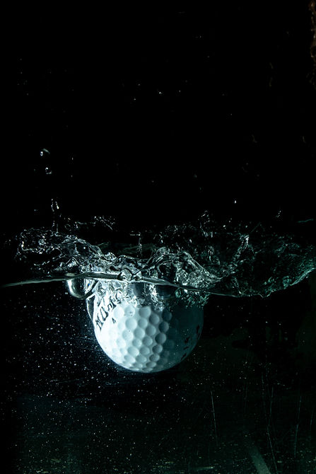 White golf ball splashed in water against black background. Image by Aryan Singh