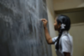 Image of girl writing on a chalkboard by Nikhita S