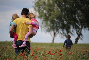 Vater mit zwei Töchtern am Arm und einem Sohn