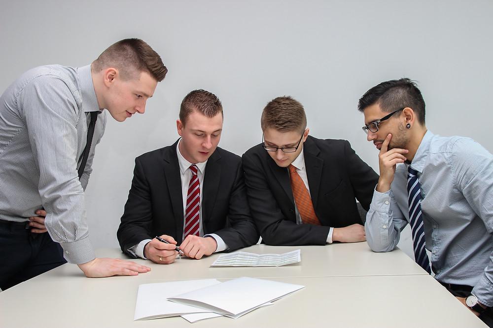 ผู้ชาย 4 คนกำลังคุยงานกันในห้องประชุม
