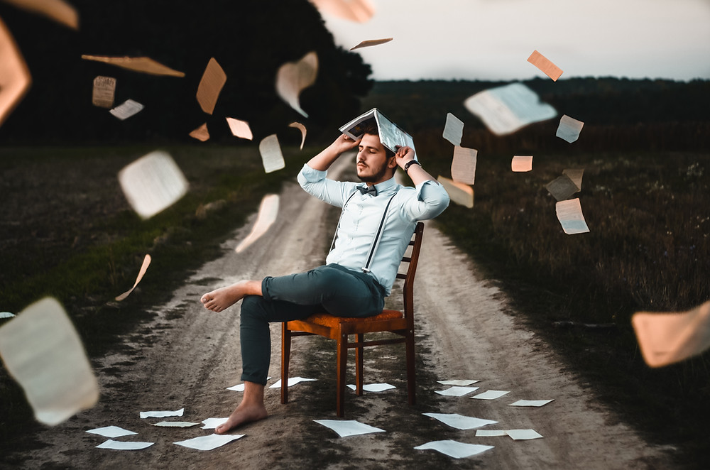 man in chair with books and pages flying around him