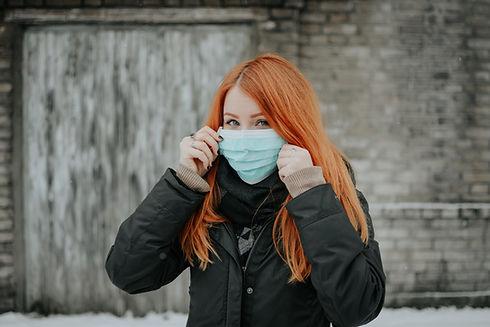 meisje met rode haren en blauw 3 laags medisch mondmasker om aan te tonen dat we in het kapsalon strikt de covid 19 maatregelen volgen en dat deze samen met andere beschermingsmiddelen verkrijgbaar zijn bij la gare du haar