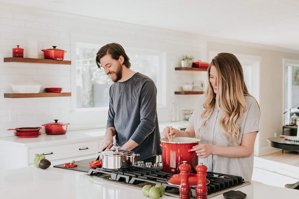A straight couple cooking together, red La Creuset kitchen items