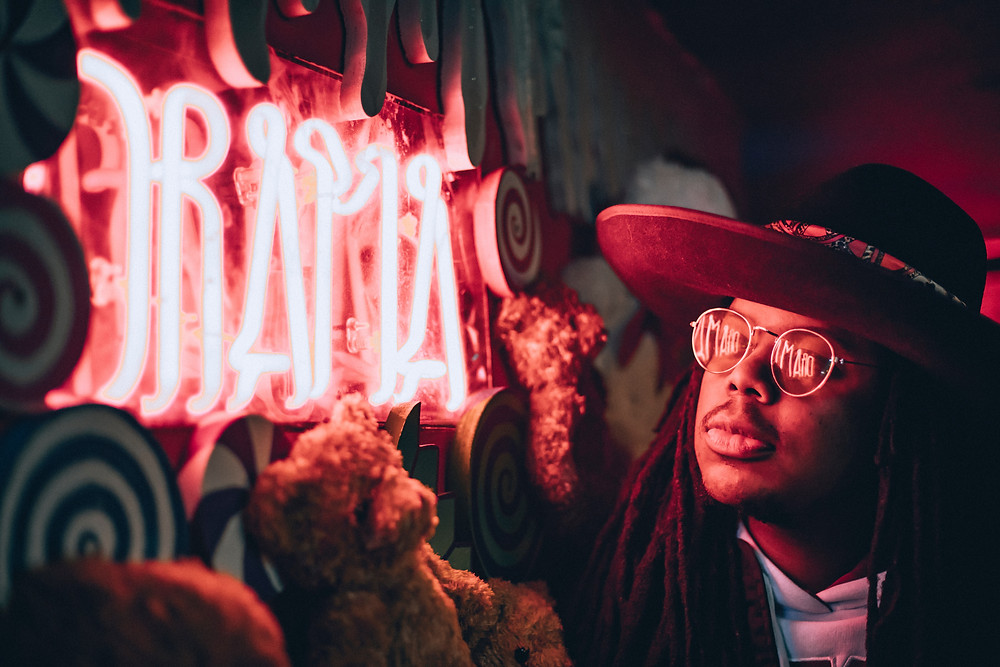 Neon Letters Spelling the Word Drama in Red light.  It looks like the sign is on a Fair Ground Wagon side, so you can imagine that this is advertising a Dramatic Adventure insie.  A Man wearing Round Glassing and a Wide Brimmed Hat is looking at the sign and you see the red light reflecting on his Glasses and the red glow from the light on his face. Teddy Bears are hanging below and to the side of the Neon Sign Too so making it look quite threatircal