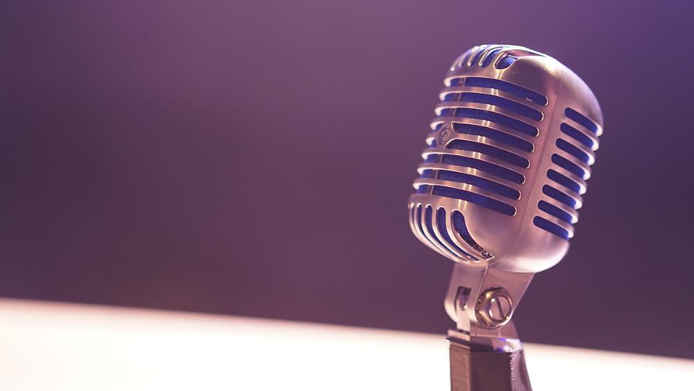 Imagem de um microfone em cima de uma mesa com o fundo escuro