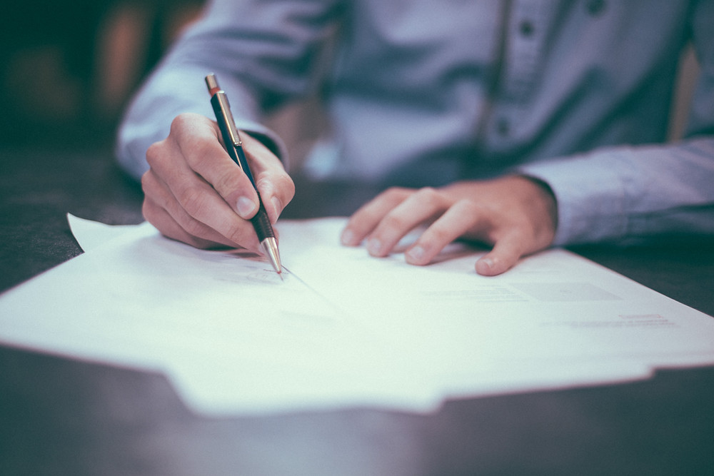 A Mans Hand Holding a Pen over some papers as if he is about to sign them.  He is wearing a blue shirt and is well groomed.