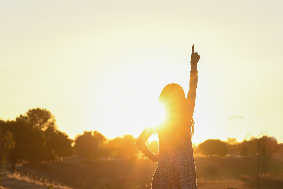 Girl pointing on top up towards the sun