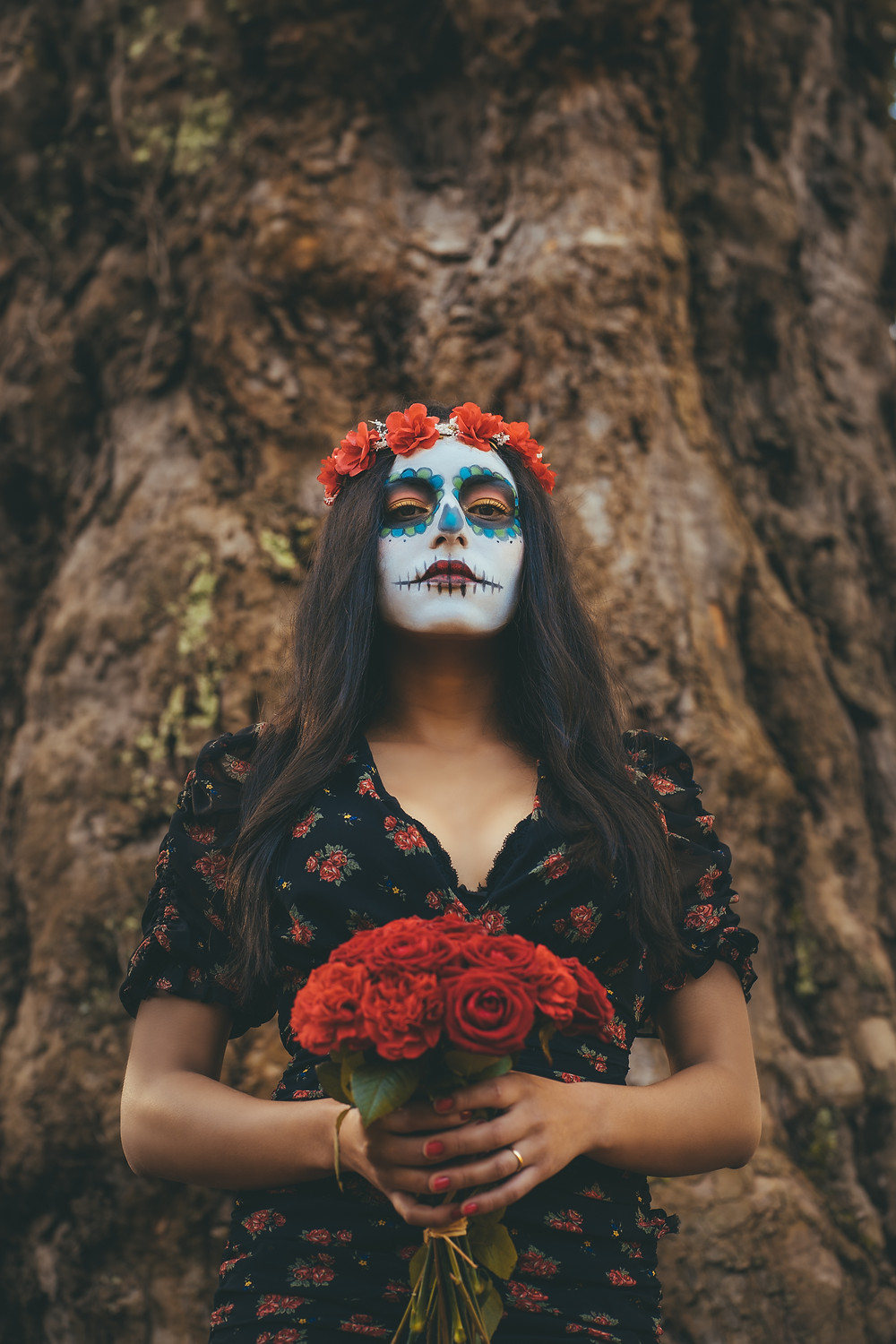 gorgeous woman dressed up a sugar skull holding flowers with a flower crown