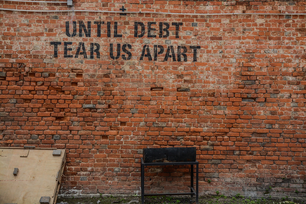 a wall with writing about debt