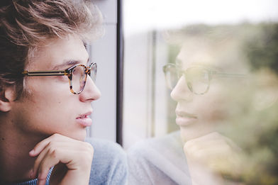 man with glasses staring out a window