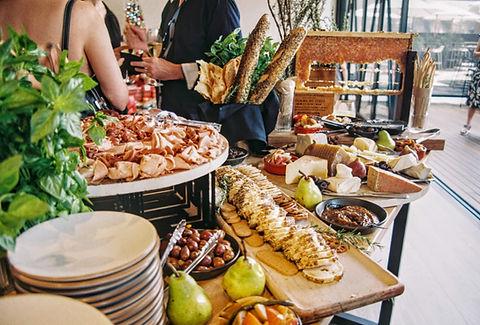 Il s'agit d'un buffet avec de la charcuterie, des olives, du pain, de la baguette ou encore du fromage. On oeut voir une pile d'assiette et des poires. Il y a un homme en chemise avec une coupe de champagne en arrière-plan