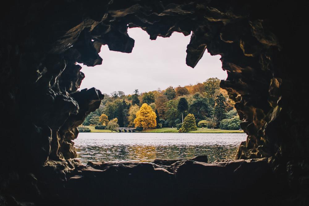 Höhle mit Ausblick auf einen Wald im Herbst.