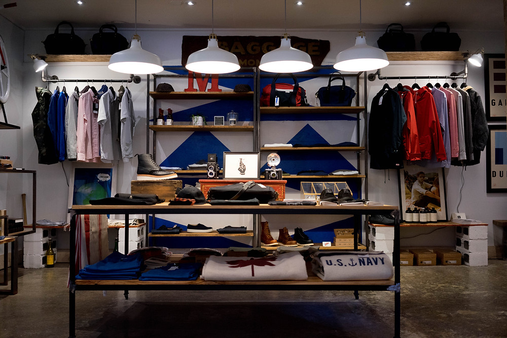 A Clothing Store. Very Contermporary looking layout with Open Hanging rails and Wood Shelfs between. In the foreground is a wooden topped metal table with clothes neatly foled and stacked on it.  Over the table hang 4 identicle lights with Grey and White shades.