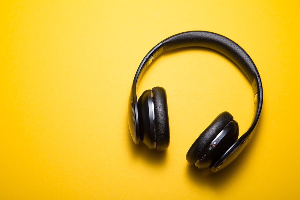 A pair of black over ear headphones lies on a bright yellow surface
