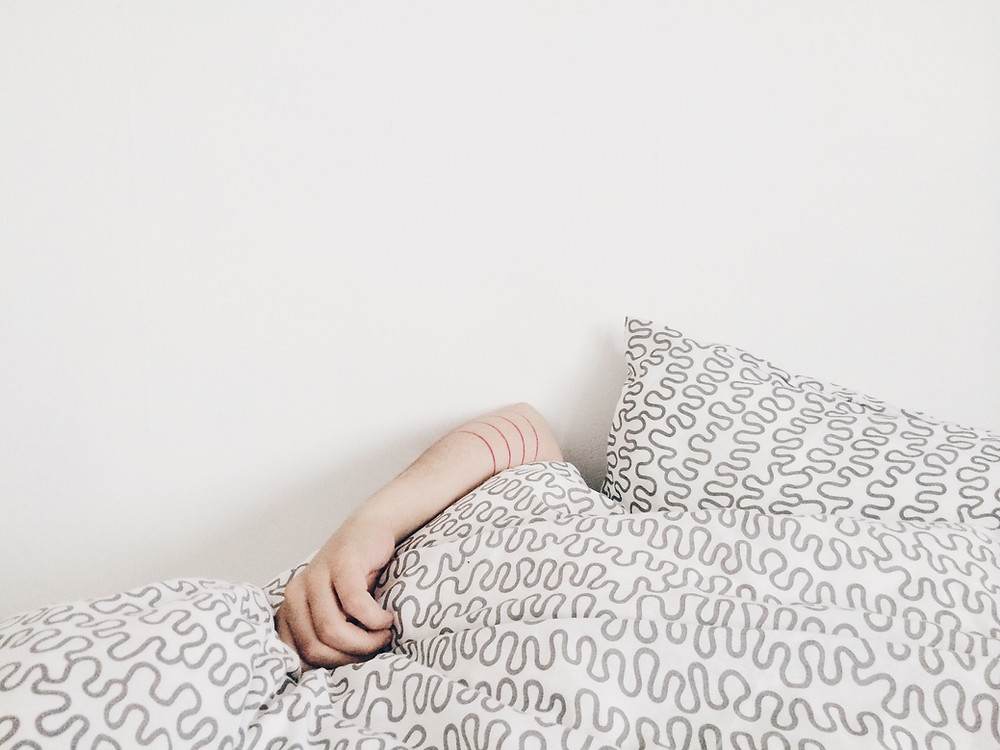 photo of woman hiding under the blankets