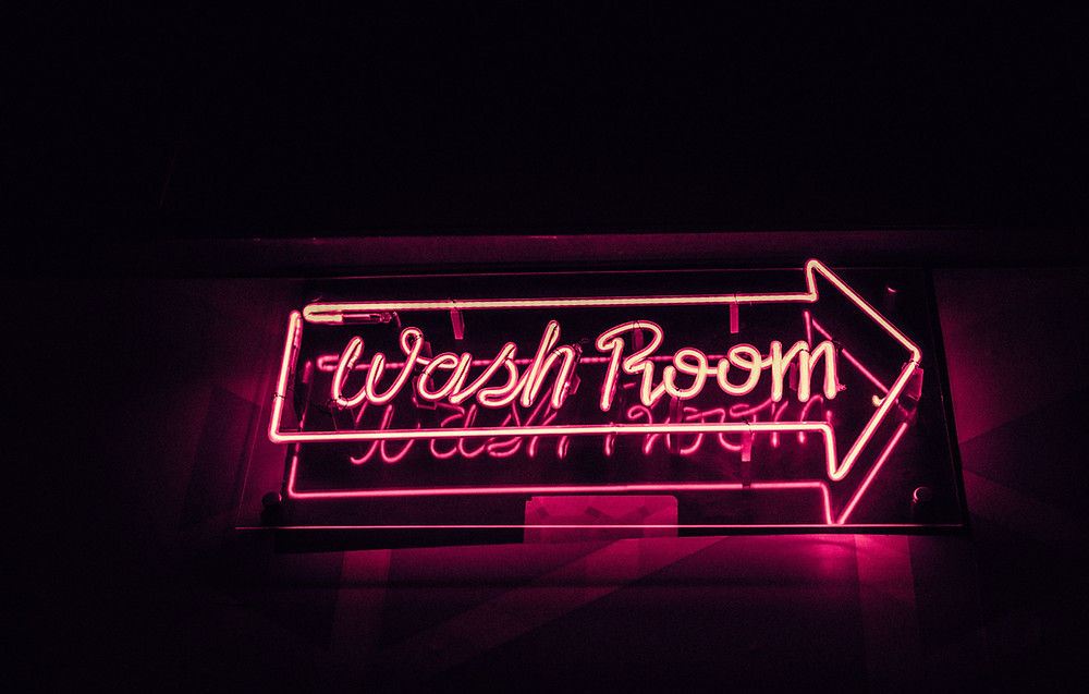 Neon pink sign pointing to washroom