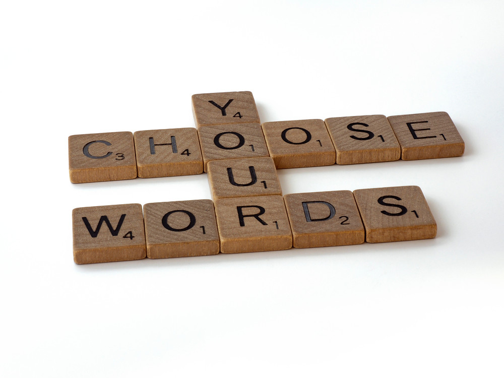 "Letter tiles from the game Scrabble spell out ""choose your words."""