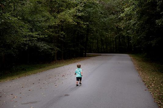 Little boy walking down a path in the woods