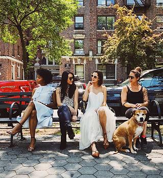 Mehrere Frauen sitzen auf einer Bank im Freien