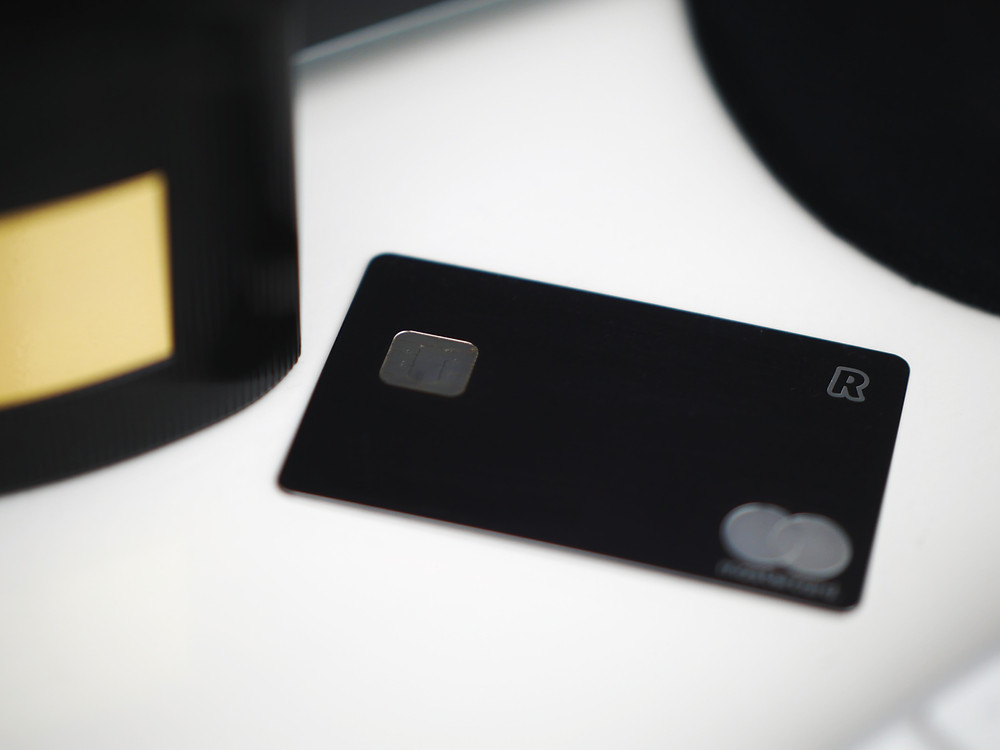 A black credit card sits on a table.