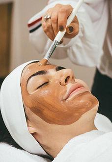 Rosto de mulher com dermatologista aplicando peeling.