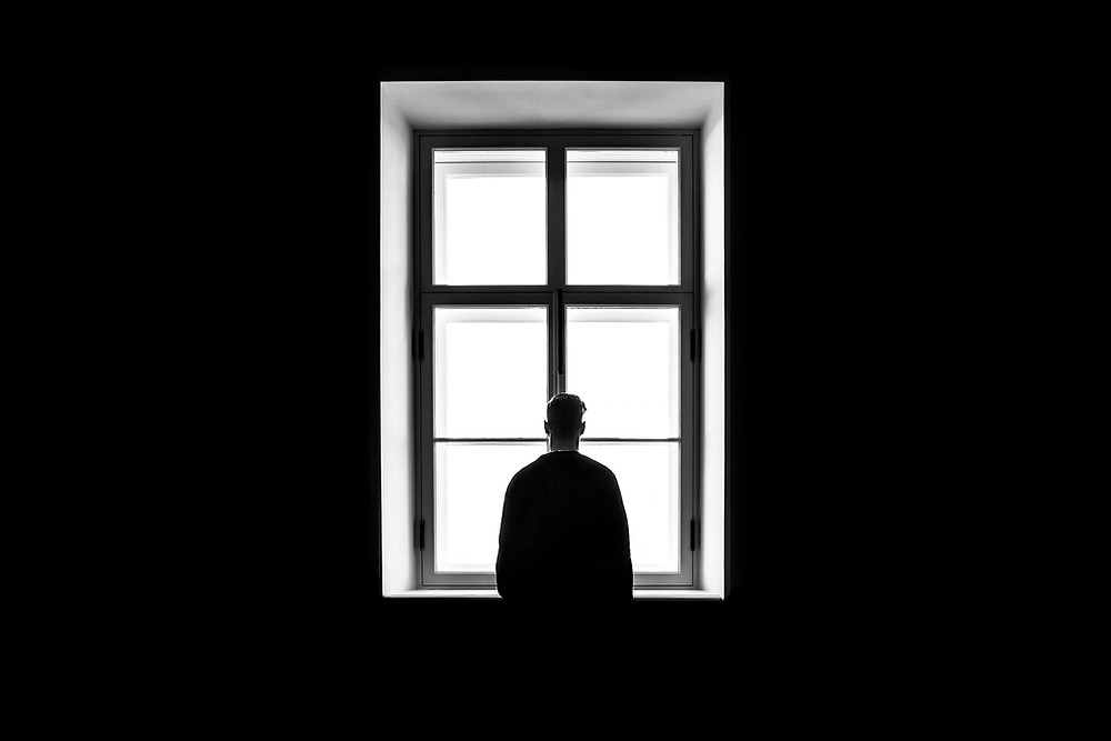 a man somberly and sadly staring out of a massive window the room iis completely dark and the only light coming from the window