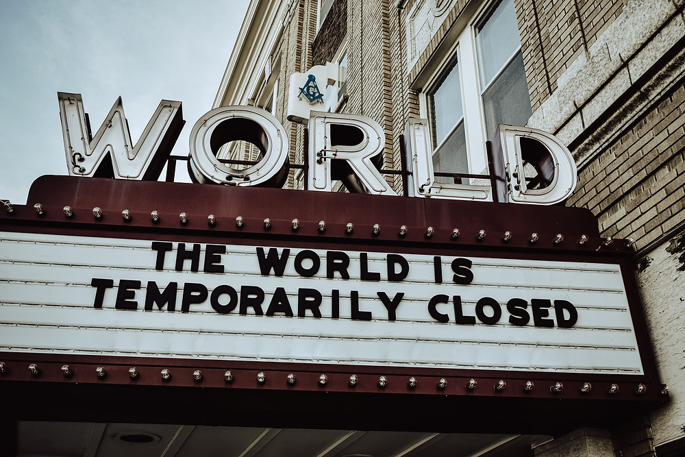 A picture with a sign that says The World is Temporarily Closed.