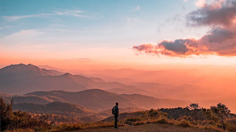 Young man gazes out over expansive rolling mountains with pink and orange colors during sunset