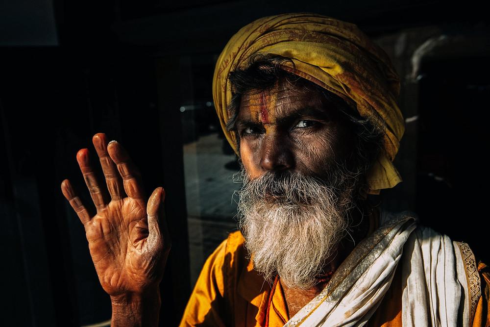 o religioso nepalês fazendo uma saudação religiosa com uma mão (número 5)