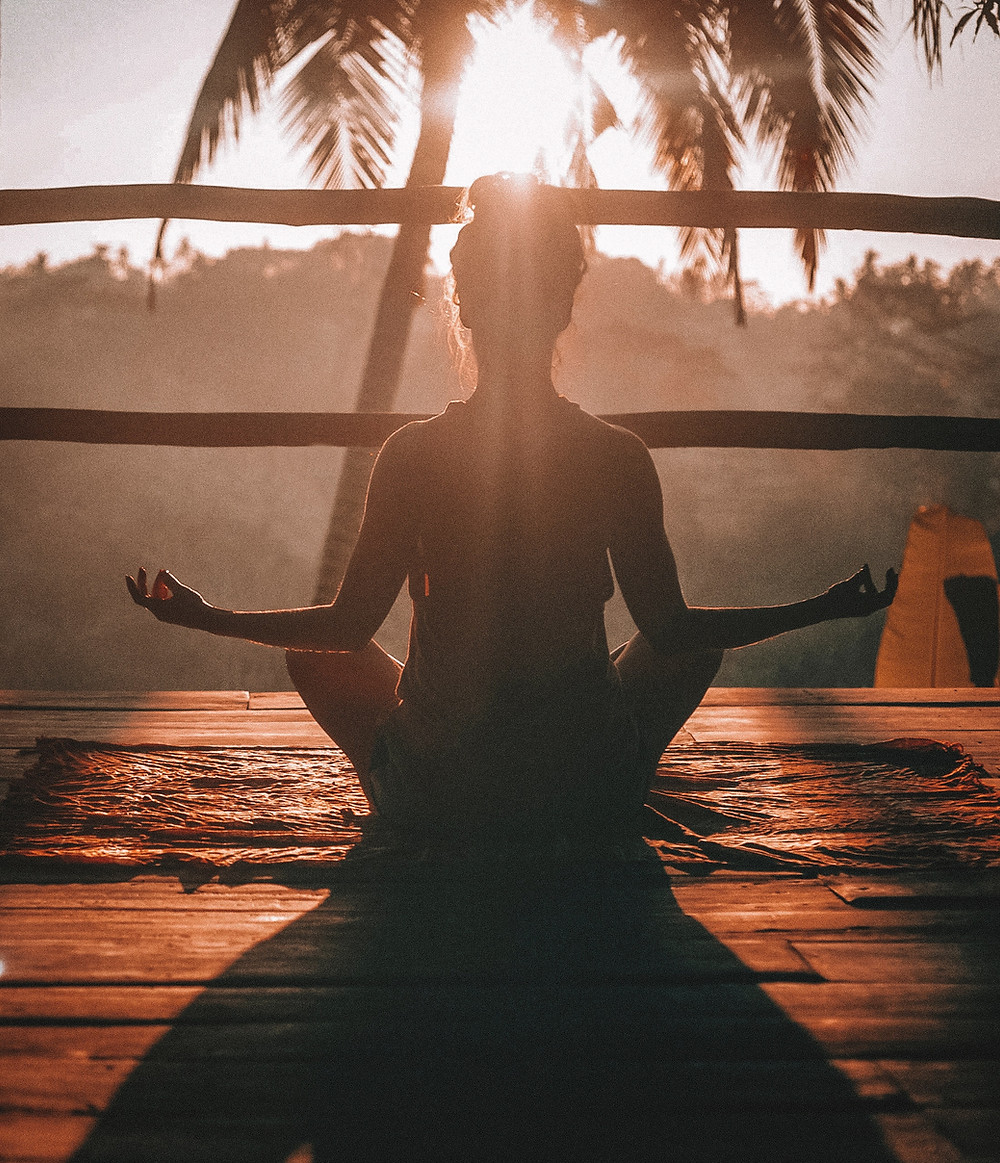 A woman doing yoga outdoors during sunrise in front of a palm tree.