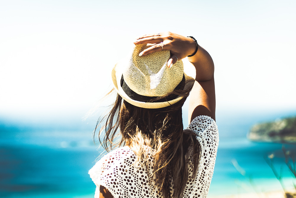 relaxed woman in straw hat overlooking the ocean