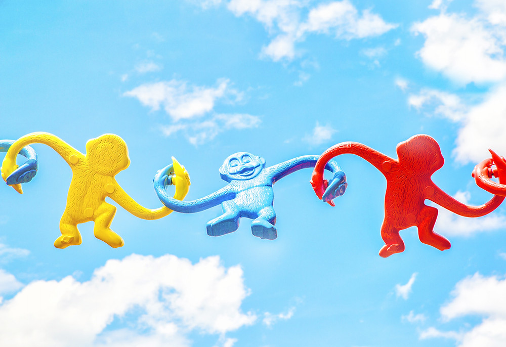Plastic monkey toys linking arms across a bright blue sky.