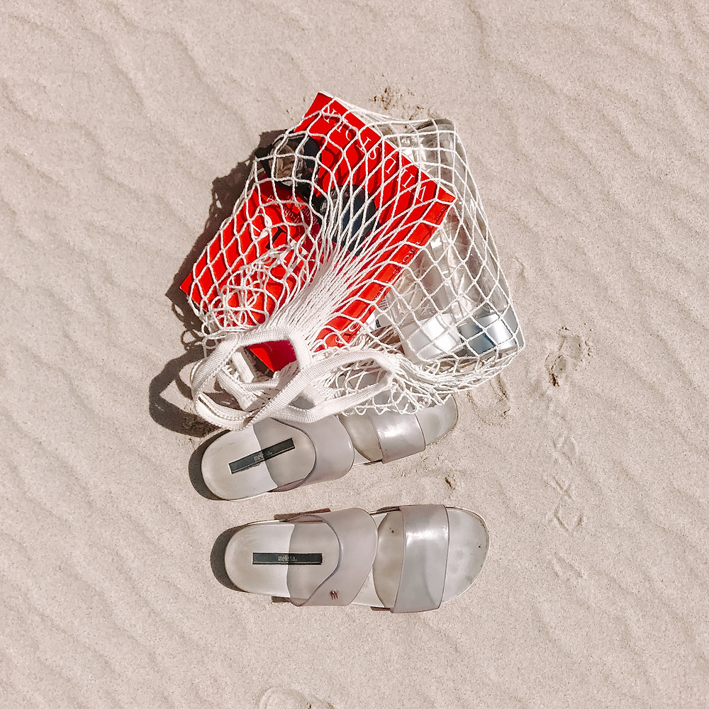 Books and a reusable water bottle are in a spaghetti net bag beside sandals on windswept beach sand.