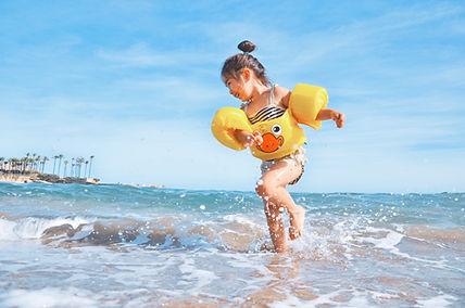 Meisje met zwembandjes om heeft plezier in de zee