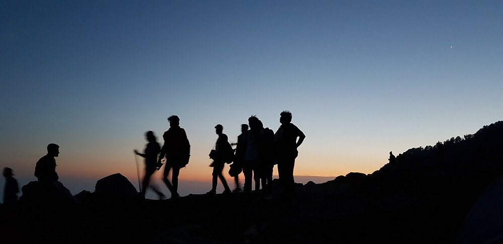 Profiles of a group of hikers on a mountain at twilight